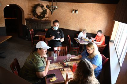Alexis Mills, waitress at Coakley's Pub, wears a masks as she takes orders from lunchtime customers inside the Havre de Grace restaurant on Wednesday, July 22.