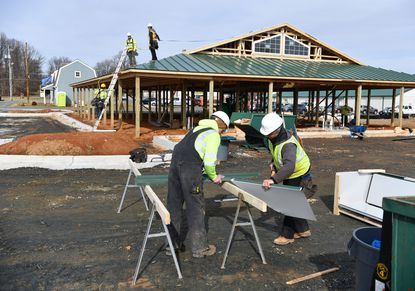 Workers install sections of a metal roof on the new Harford County agri-business incubator building, called The Grove, Thursday morning. The building is located next to the Harford County Agricultural Center in Street.