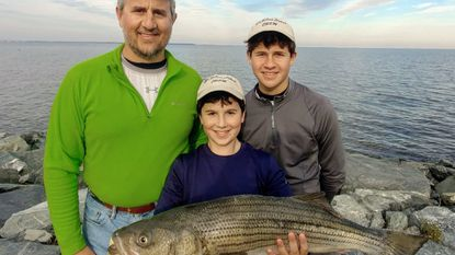 (L to R) Annapolis residents Jason Zagalsky and sons Darin (holding fish) and Brian enjoyed a great fall catching big stripers. (Courtesy photo) - Original Credit:
