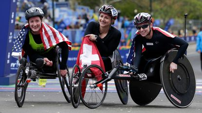 From left, second-place finisher Tatyana McFadden, first-place finisher Manuela Schar and third-place finisher Amanda McGrory pose for a picture at the finish line of the New York City Marathon in New York, Sunday, Nov. 5, 2017.