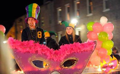 Dave Johnson, left, and Carley Bayes ride atop a float by local boutique Pizzazz! during the Mardi Gras parade in Havre de Grace, Md.