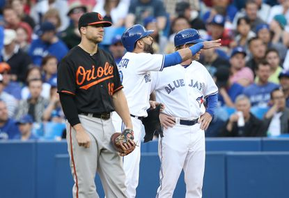 Toronto Blue Jays right fielder Jose Bautista reacts as he is heckled by Orioles pitcher Bud Norris from the dugout. Chris Davis listens.