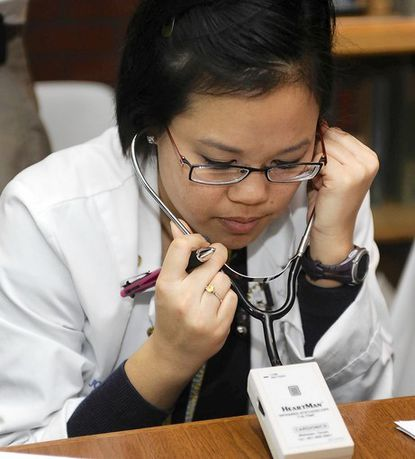 Dr. Melissa Kwan, a pediatric emergency physician, listens as Dr. Reid Thompson, a pediatric cardiologist at Johns Hopkins Childrens Center, teaches a workshop for physicians about using stethoscopes to detect heart problems. She is using stethophone, which is equipped with recorded sounds from real cardiac patients with various conditions.