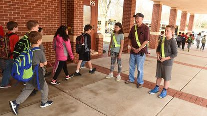 Harry Griffith, serving as an honorary officer for the day, stands between current 5th grade safety patrol officers, Capt. Carlie Rohrer, left, and Lt. Kenny Kuhne as students exit the school during dismissal at Spring Garden Elementary School on Friday.