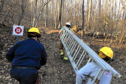 Rescue personnel from the Jarrettsville Volunteer Fire Company hustle toward the King and Queen Seat in Rocks State Park, where a rock climber was reported stuck Tuesday afternoon.