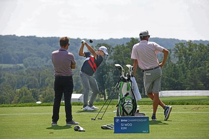 Golfer Si Woo Kim, center, practices at the driving range to prepare for the BMW Championship at the Caves Valley Golf Club on Monday August 23, 2021.