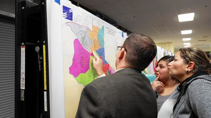 Community members consider a map reflecting the current boundaries of southwest area elementary schools during a public information sesson on Nov. 18 at Catonsville High School.