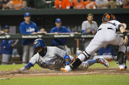 Toronto Blue Jays shortstop Jose Reyes slides under Orioles catcher Caleb Joseph tag to score during the fifth inning at Oriole Park at Camden Yards.