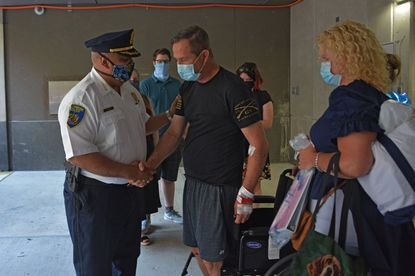 Baltimore Police officer Brian Burke is discharged from the hospital a week after he was shot in the line of duty.