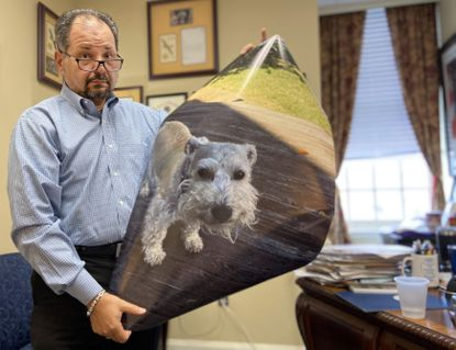 Pasadena resident Laurence Sanders prepares to tell lawmakers about Buddy the miniature schnauzer, who died after being shot by a BB gun in 2018. Sanders is advocating for a bill that would increase the amount a person could seek in damages from $10,000 to $25,000 in cases of animal abuse, torture and death.
