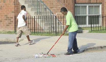 Green team member Kevin Wellons, 14, sweeps up trash on Hamburg St. There needs to be more focus on solutions for trash and other problems in Baltimore.