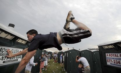 A Preakness reveler reaches for something to grab onto after coming up short while trying to leap from one portable toilet to another in the Pimlico Race Course infield.