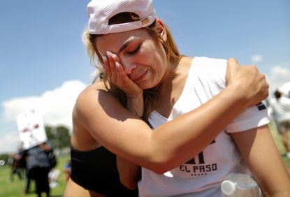 El Paso residents Cassandra Anchondo, right, and Leslie Rodriguez hug at a protest against President Donald Trump's visit, following a mass shooting which left at least 22 people dead on August 7.