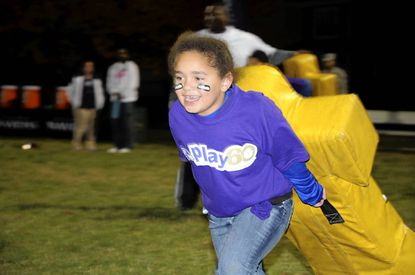 Shyanne Surette, 7, of Aberdeen, pulls a tackling dummy during an NFL Play 60 football clinic with Baltimore Ravens players at Aberdeen Proving Ground Tuesday.