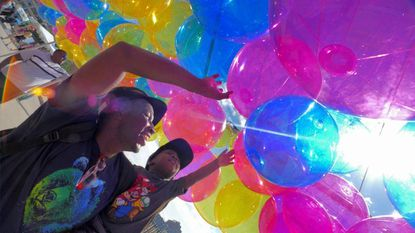 """Baltimore, MD -- Carl Washington of Laurel holds his son Carter Washington, 2 beneath a sea of multi-colored balloons of the """"Choose Your Own Adventure"""" installation at 2018 Artscape."""