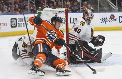 The Blackhawks' Slater Koekkoek tries to stop the Oilers' Colby Cave as goalie Robin Lehner makes the save on Feb. 11, 2020, in Edmonton, Alberta. Cave recently suffered a brain bleed and is in a coma.