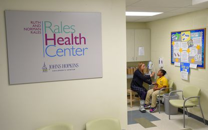 Nurse practitioner Tresa Schumann tends to Morgan Thompson, at the time a second grader at the Rales Health Center at a school in Baltimore when it opened at the school in 2015.