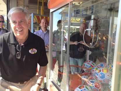 Republican gubernatorial candidate Larry Hogan laughs as he loses a soccer ball in a claw game at Ocean City boardwalk as he decries proposed regulations about campaigns.