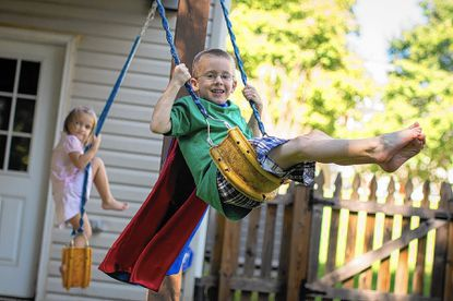 Sean Smole, 6, wears his Superman cape as he swings under the family deck with his sister Sydney, 4,.