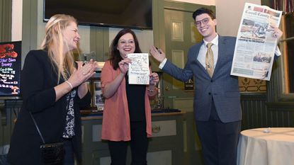 Mentalist Dan Eckhart, right, with help from audience members Christina Burgess, left, and Tina Rivenbark, both of Sykesville, reveals his predictions for Friday's Carroll County Times front page during his performance at Baldwin's Station.