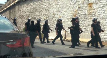 Dozens of corrections officers in tactical gear enter the Baltimore jail complex Monday afternoon to extract those responsible for a melee that Sunday night that left eight corrections officers and six detainees injured.