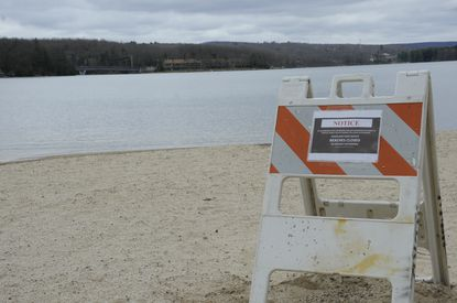A sign placed by the Maryland Park Service notifies beachgoers that Deep Creek Lake State Park beaches are closed to limit the spread of the new coronavirus in this photo taken March 31, 2020.