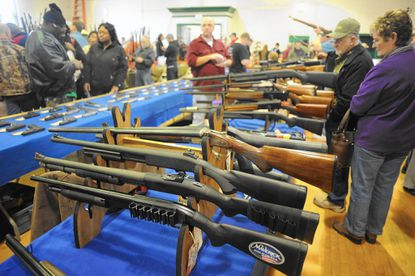 Patrons check out a vendor's selection of firearms during last year's Bel Air Gun Show at the Bel Air Reckord Armory. The gun show returns this weekend, Friday, Saturday and Sunday.