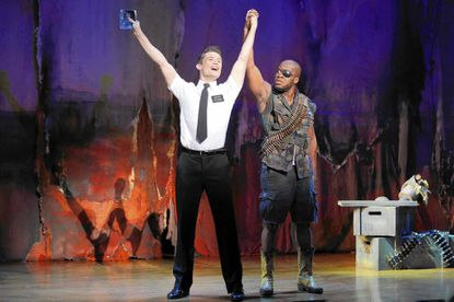 "Mark Evans, left, as missionary Elder Price; and Derrick Williams as a Ugandan warlord in ""The Book of Mormon."""