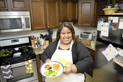 Shannon Montague shows off the chicken dish she made from ingredients delivered to her home in Towson.