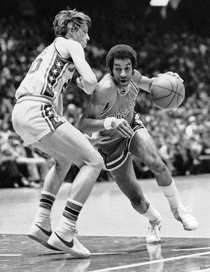 In this file photo, Chicago Bulls guard Norm Van Lier (right) dribbles past Philadelphia 76ers forward Doug Collins. Van Lier died Feb. 26, 2009, the Cook County medical examiner's said. He was 61. Chicago Fire Department spokesman Quention Curtis says firefighters responding to a request for a well-being check found Van Lier unresponsive shortly before 1 p.m. He was pronounced dead at the scene.
