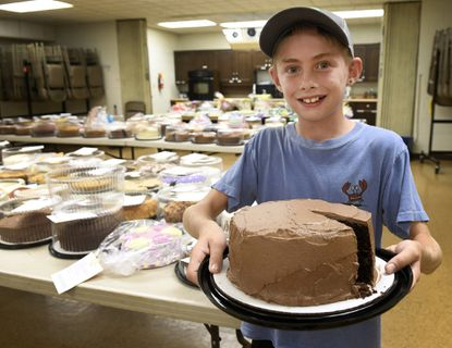 Joey Battaglia, 11, of the Pleasant Valley 4-H Cub shows off his grand champion baked good, a bacon chocolate cake, at the Carroll County 4-H & FFA Fair in Westminster Wednesday, July 31, 2019.