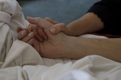 Donna Williams holds her husband Ken Williams, 67, hand two days before he died at a hospice in Santa Barbara, Calif. on June 10.