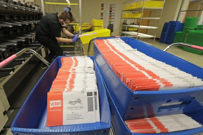 Vote-by-mail ballots are shown in sorting trays, Wednesday, Aug. 5, 2020, at the King County Elections headquarters in Renton, Wash., south of Seattle. Never in U.S. history will so many people exercise the right on which their democracy hinges by marking a ballot at home. (AP Photo/Ted S. Warren)