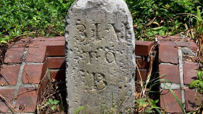 """This milestone, a remnant of an early Maryland turnpike, is being relocated during widening of Rte. 97 north of Westminster. Even after standing over 200 years along a heavily-traveled road, you can still read """"31 M to B"""" – the distance to Baltimore."""