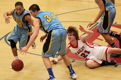 Centennial's Bradley Benson, right, loses the ball to River Hill's Tre Patterson, left, and Walt Moody, center, during their game Wednesday. River Hill won in overtime, 55-51.