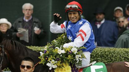 Jockey Edgar Prado sits atop Runhappy in the winner's circle after winning the Breeders' Cup Sprint horse race at Keeneland race track Saturday, Oct. 31, 2015, in Lexington, Ky.
