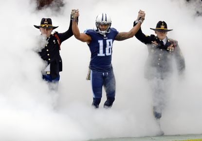 Titans wide receiver Rishard Matthews (18) holds hands with soldiers as he takes the field before a game against the Bengals Sunday, Nov. 12, 2017, in Nashville, Tenn.