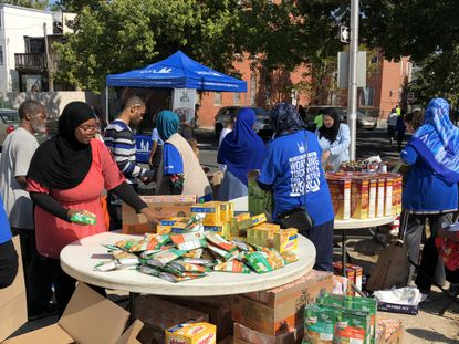 """Volunteers hand out food outside Masjid al Haqq mosque in West Baltimore as part of Islamic Relief USA's """"Day of Dignity"""" events around the country."""