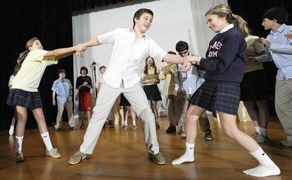 """Michael Horn, as Conrad Birdie, is torn between two women, Ali Dowell, Cabrini Class, who portray his teenage fans, as the St. James Academy middle-schoolers rehearse a scene from """"Bye Bye Birdie"""" Feb. 3 at the Monkton school. The public is invited to see the musical performed at the school on Feb. 17, 18 and 19."""