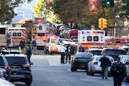 Police officers inspect a truck following an attack in New York on Tuesday that left eight people dead. On Wednesday, President Donald Trump blamed the attack on the nation's diversity visa program.