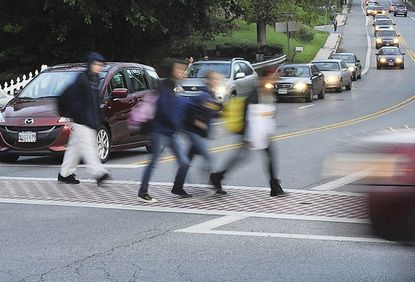 Catonsville High School students cross South Rolling Road at Blomsbury Avenue on Oc t. 3 as rush hour traffic begins to build. The county plans to install one of its 15 speed cameras along South Rolling Road near the school.