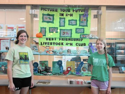 Jennifer Brigante, left, and Emily Buckley show off their 4-H Club display in the show case at the Glenwood Library.