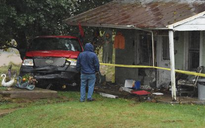 A person examines the results of an automobile accident onto the front porch of a home on S. Clear Ridge Road on a rainy Wednesday afternoon in New Windsor.