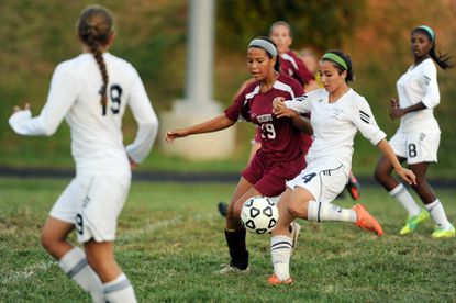 Perry Hall's Maria Ambridge, right, gets off a shot on goal despite pressure from Alyx Oakley, of Hereford.