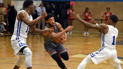 Edmondson's Keith Bolden, center, runs with the ball as Patterson's Jalen Willis, left, and Zaccheus Blackwell, right, guard at Patterson High School in first half action.
