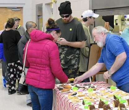 "<font color=""black"">Sam Stuart serves </font><font color=""black"">desserts</font><font color=""black""> at the Loves and Fishes meal served at the Ascension Episcopal Church in Westminster on Wednesday January 25, 2016 during the Point in Time Homelessness Count.</font>"