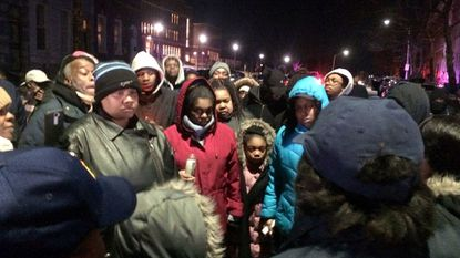 Keyona Weaver, in red and holding a camera, is surrounded by friends and family Tuesday night during a vigil for her young son and daughter who died in a house fire last week in West Baltimore.
