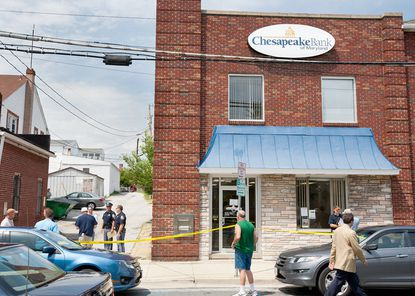 Police and local residents stand outside the scene of a robbery at the Chesapeake Bank of Maryland in Arbutus on Friday. The criminals escaped on foot down the alley to the left off of Carville Avenue following the robbery, police said.