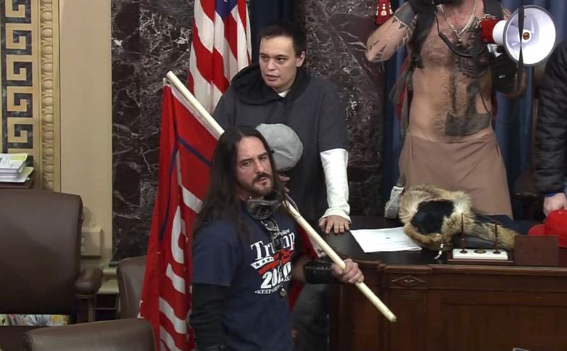 In this file image from U.S. Capitol Police video, Paul Allard Hodgkins, 38, of Tampa, Fla., front, stands in the well on the floor of the U.S. Senate on Jan. 6, 2021, at the Capitol in Washington.