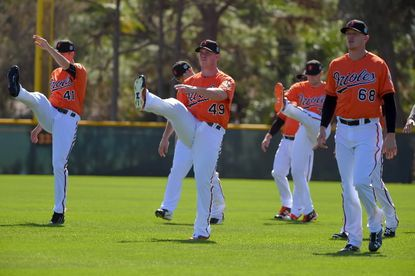 Sarasota, FL -- 02/19/2016 -- Baltimore Orioles players (from left) Andy Oliver (41), Dylan Bundy (49) and Parker Bridwell (68) loosen during the first official day of spring training practice at the Ed Smith Stadium complex.